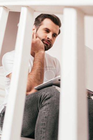 Photo pour Concentration sélective du télétravailleur à l'aide d'un ordinateur portable sur l'escalier à la maison - image libre de droit