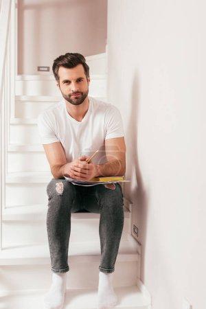 Photo pour Beau homme tenant crayon et livre avec des documents sur l'escalier à la maison - image libre de droit