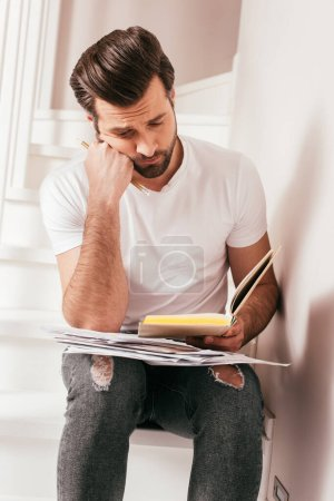 Photo pour Beau livre de lecture freelance et détenant des documents sur l'escalier à la maison - image libre de droit