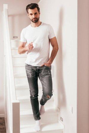 Photo pour Beau homme tenant une tasse de café et regardant la caméra sur l'escalier à la maison - image libre de droit