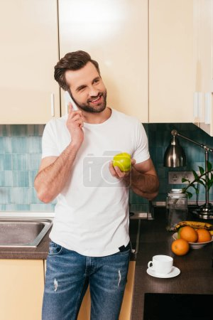 Sonriente hombre hablando en el teléfono inteligente y sosteniendo manzana en la cocina