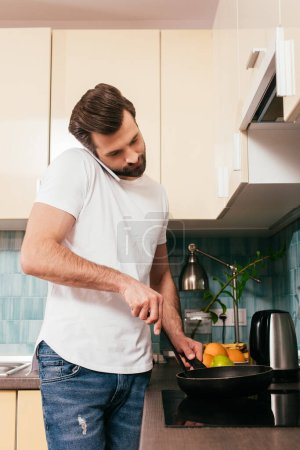 Photo for Man talking on smartphone and preparing breakfast in kitchen - Royalty Free Image
