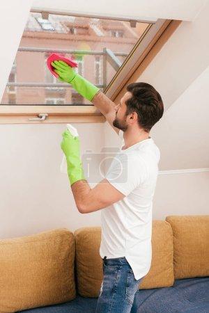 Photo pour Vue latérale de l'homme utilisant du détergent et du chiffon pendant le nettoyage de la fenêtre dans le salon - image libre de droit