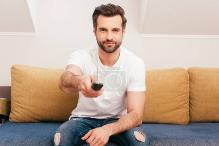 Handsome man using remote controller while clicking channels on couch