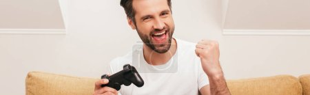 Photo for KYIV, UKRAINE - APRIL 14, 2020: Cheerful man holding joystick and showing yeah gesture at home, panoramic shot - Royalty Free Image