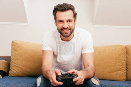 KYIV, UKRAINE - APRIL 14, 2020: Handsome man smiling at camera and holding joystick on sofa at home