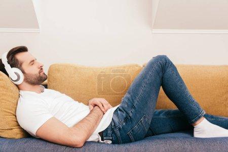 Photo pour Vue latérale d'un bel homme écoutant de la musique dans un casque alors qu'il était allongé sur un canapé - image libre de droit