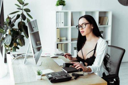 Photo pour Secrétaire sensuelle utilisant le téléphone au travail près d'un ordinateur et papier au bureau - image libre de droit
