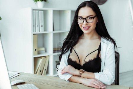 Photo pour Focus sélectif de secrétaire sexy en soutien-gorge et lunettes souriant à la caméra dans le bureau - image libre de droit