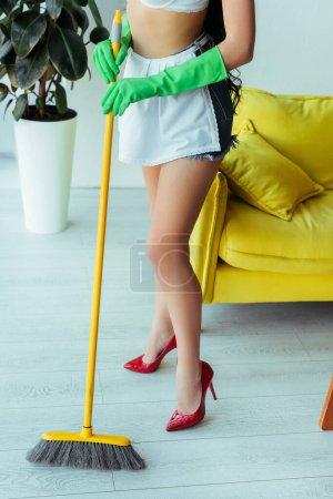 Photo pour Vue recadrée de femme sexy en chaussures à talons hauts tenant balai à la maison - image libre de droit