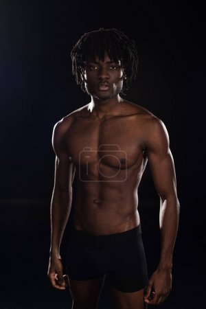 Photo for Handsome shirtless african american man isolated on black with back light - Royalty Free Image