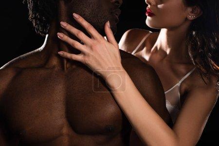 Photo pour Vue recadrée de femme passionnée étreignant nu afro-américain copain isolé sur noir - image libre de droit