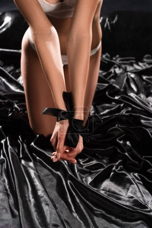 Photo for Cropped view of seductive girl with bound hands on black silk bed - Royalty Free Image