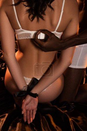 Photo pour Crochet vue d'un Africain américain et d'une séduisante femme les mains liées sur le lit dans l'obscurité - image libre de droit