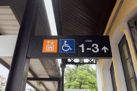 Signs and symbols on nameplate of train station in Catalonia, Spain