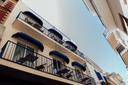 Photo for Low angle view of tables and chairs on balcony of building with blue sky at background in Catalonia, Spain - Royalty Free Image