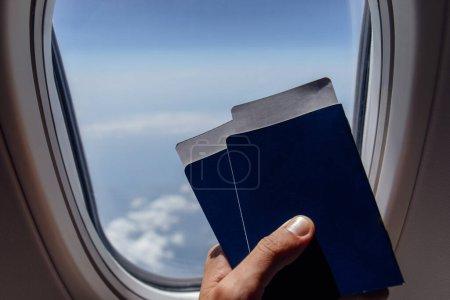 Photo pour Vue en coupe d'un homme tenant des passeports et des billets d'avion près d'un hublot d'avion - image libre de droit