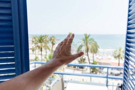 Photo pour Vue coupée de la main mâle près de la porte ouverte avec la côte de la mer et des palmiers en arrière-plan en Catalogne, Espagne - image libre de droit