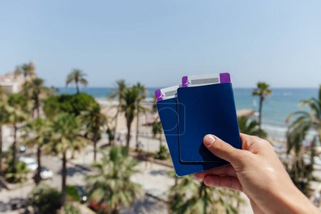Photo for Cropped view of man holding passports and air tickets with palm trees and sea coast at background - Royalty Free Image
