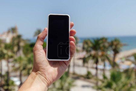 Photo pour Vue recadrée de l'homme tenant smartphone avec des palmiers et la côte de la mer en arrière-plan - image libre de droit