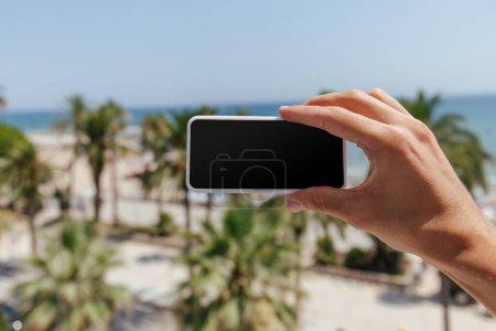Photo pour Vue en plan d'un homme tenant un smartphone avec écran vierge et bord de la mer en arrière-plan - image libre de droit
