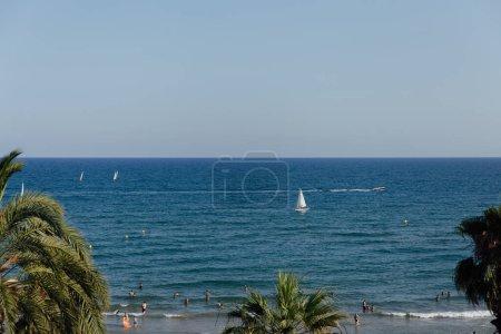 Photo pour CATALONIE, ESPAGNE - 30 AVRIL 2020 : Les gens se reposent sur la plage avec des palmiers et des yachts en mer en arrière-plan - image libre de droit