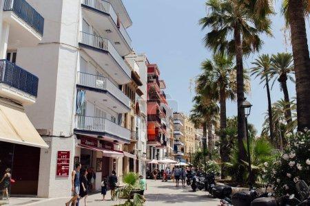 Foto de CATALONIA, ESPAÑA - APRIL 30, 2020: Gente caminando por la calle urbana con palmeras y cafetería al aire libre. - Imagen libre de derechos