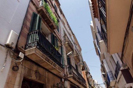 Photo pour Vue à faible angle de la rue urbaine avec plantes et lanterne sur la façade en Catalogne, Espagne - image libre de droit