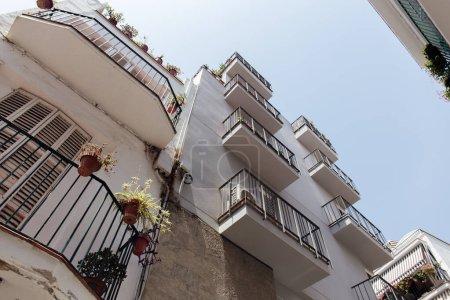 Photo pour Vue à faible angle des façades blanches de bâtiments avec ciel bleu à l'arrière-plan en Catalogne, Espagne - image libre de droit