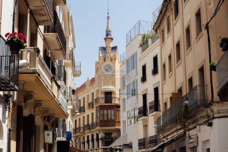 Urban street with clock on chapel and blue sky at background in Catalonia, Spain