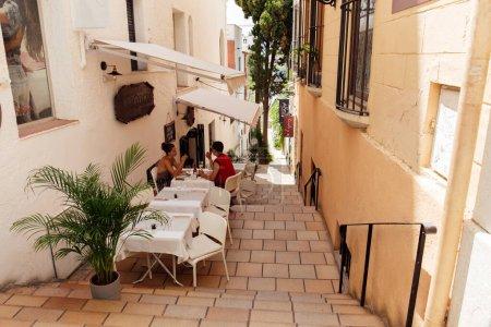 Photo pour CATALONIE, ESPAGNE - 30 AVRIL 2020 : Des gens assis à table dans un café en plein air près de maisons dans une rue urbaine - image libre de droit