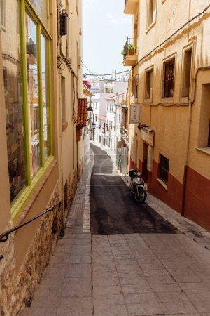 Photo pour Scooter près de bâtiments sur la promenade de la rue urbaine en Catalogne, Espagne - image libre de droit