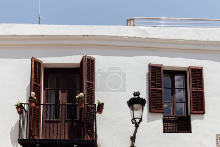 Photo for White facade of building with wooden shutters on window and balcony door in Catalonia, Spain - Royalty Free Image