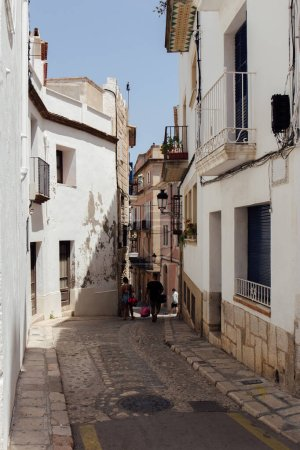 Photo for CATALONIA, SPAIN - APRIL 30, 2020: People walking on urban street with paving stones on walkway - Royalty Free Image