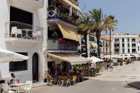 Photo for CATALONIA, SPAIN - APRIL 30, 2020: Urban street with outdoor cafe and palm trees in Catalonia - Royalty Free Image