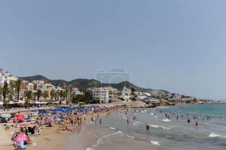 CATALONIA, SPAIN - APRIL 30, 2020: People resting on sandy beach and swimming in sea near buildings and palm trees on coast