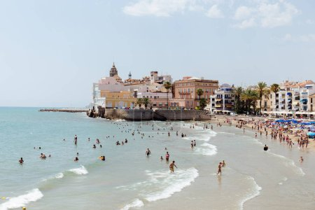 Photo pour CATALONIE, ESPAGNE - 30 AVRIL 2020 : Personnes nageant en mer près de bâtiments et de palmiers sur la plage - image libre de droit