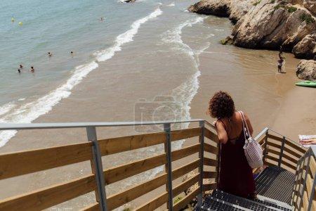 Photo pour CATALONIE, ESPAGNE - 30 AVRIL 2020 : Présence sélective d'une femme debout sur un escalier avec une plage de sable et la mer en arrière-plan - image libre de droit