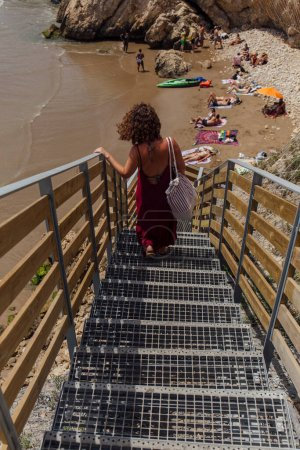 Photo pour CATALONIE, ESPAGNE - 30 AVRIL 2020 : Mise au point sélective de la femme marchant sur l'escalier sur la plage avec des pierres - image libre de droit