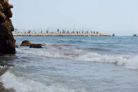 Photo pour Pierres et vagues sur la côte avec jetée et bateaux à l'arrière-plan en Catalogne, Espagne - image libre de droit