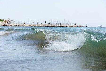 Photo pour Concentration sélective des vagues sur le littoral avec jetée et palmiers à l'arrière-plan, Catalogne, Espagne - image libre de droit