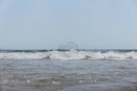 Selective focus of sea with waves and blue sky at background in Catalonia, Spain