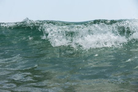 Photo for Close up view of sea wave with foam and blue sky at background - Royalty Free Image