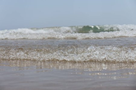 Selective focus of wave on wet sandy beach with blue sky at background
