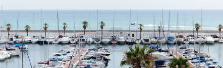 CATALONIA, SPAIN - APRIL 30, 2020: Palm trees near yachts in port with seascape at background, panoramic shot
