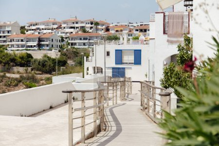 Selective focus of walkway with railing on urban street with houses in Catalonia, Spain