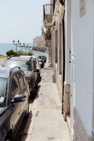Photo pour Rue urbaine avec rangée de voitures, bâtiments et mer à l'arrière-plan en Catalogne, Espagne - image libre de droit