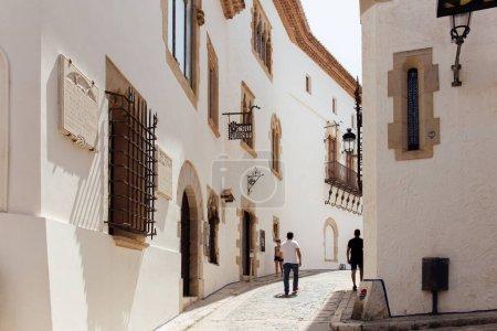 Photo pour CATALONIE, ESPAGNE - 30 AVRIL 2020 : Personnes marchant sur les rues ensoleillées à proximité de bâtiments aux façades blanches - image libre de droit