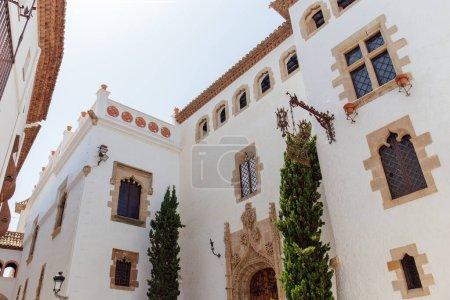 Photo pour Vue à faible angle des arbres près d'un bâtiment à façade blanche en Catalogne, Espagne - image libre de droit