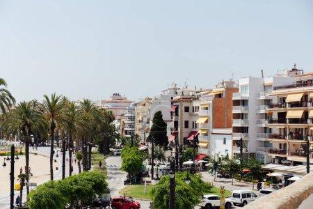 Photo pour CATALONIE, ESPAGNE - 30 AVRIL 2020 : Rue urbaine avec bâtiments, palmiers et ciel bleu en arrière-plan - image libre de droit
